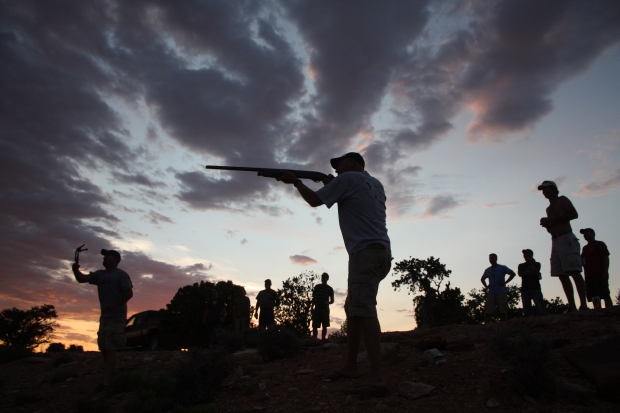 Skeet shooting competition at dusk.
